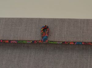 This mini pelmet over a Roman blind is embellished with looped piping in Liberty's Marky B Tana Lawn