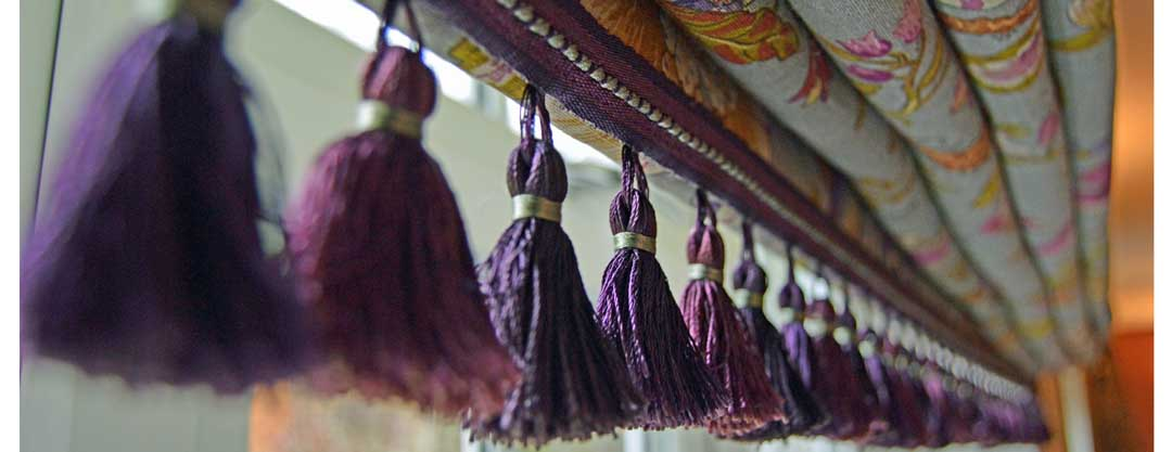 Roman blind with rich, berry coloured tassel fringe